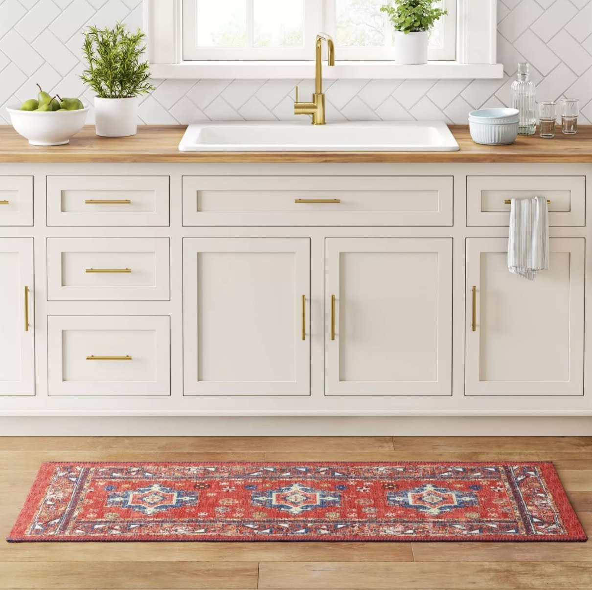 A red and blue Persian style rug in front of a kitchen sink