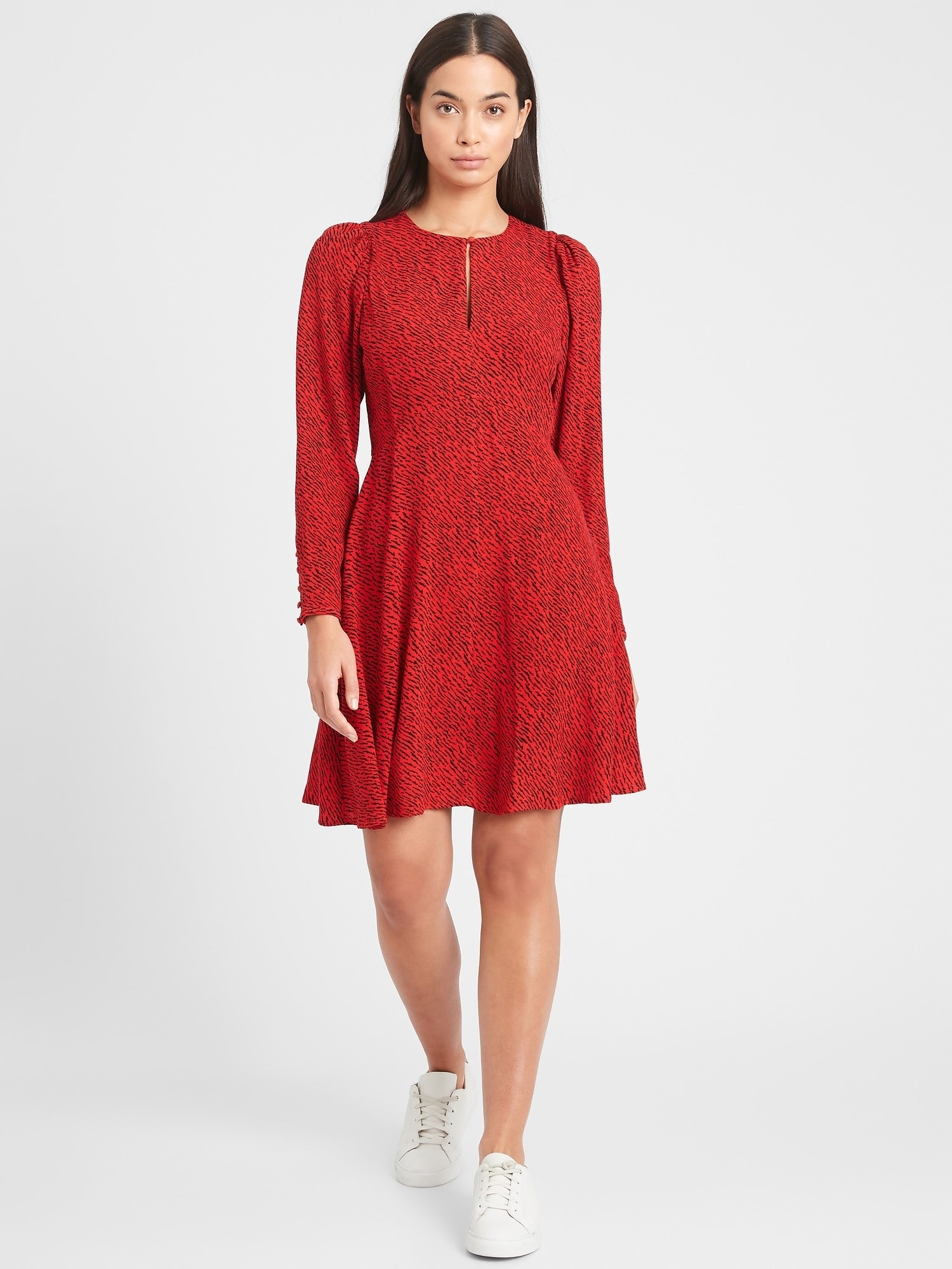 Model wearing the knee-length long-sleeved dress with long key hole in the front in red with a black pattern all over it