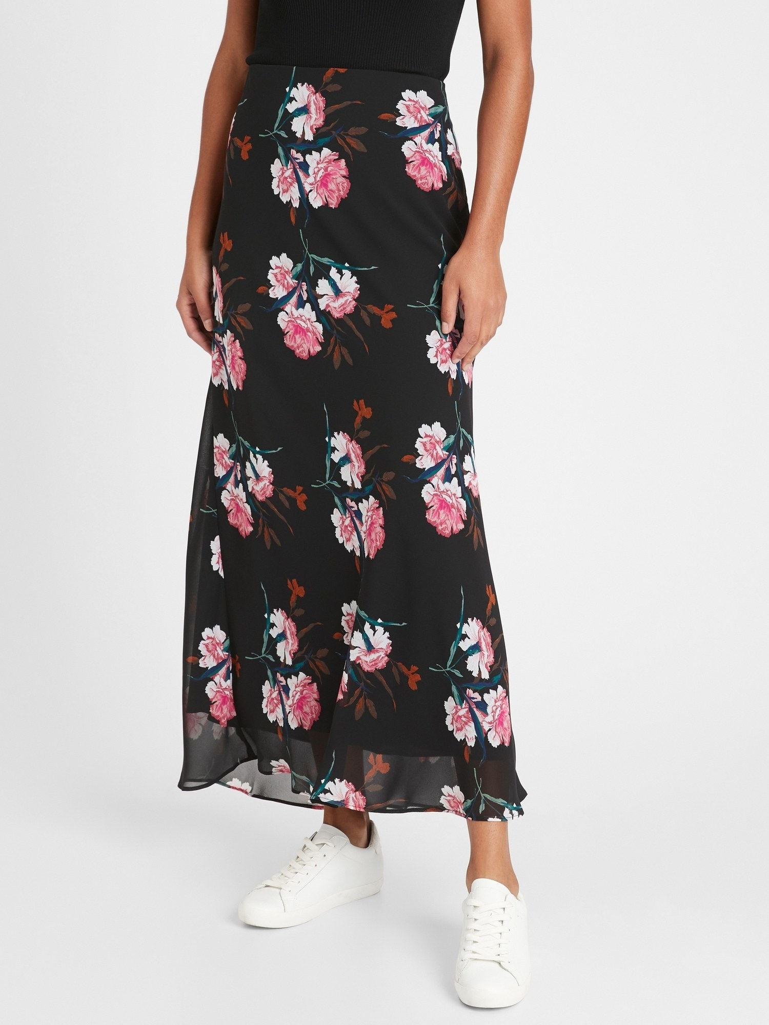 Model wearing the ankle-length maxi skirt in black with white and pink flowers all over it