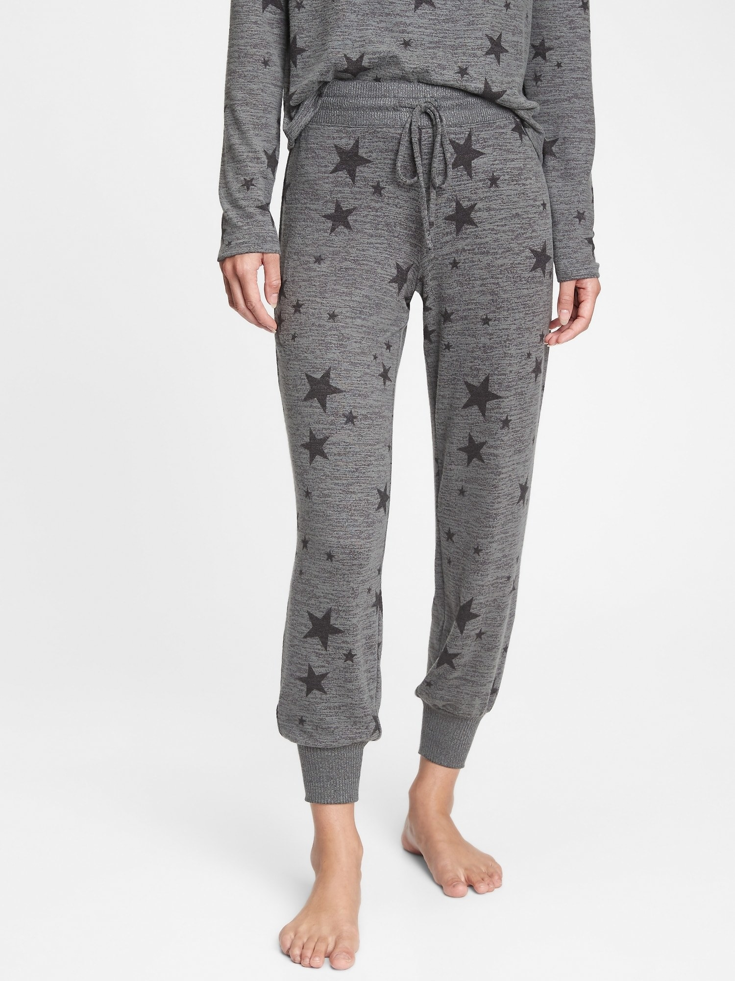 model wearing soft knit joggers in charcoal grey stars
