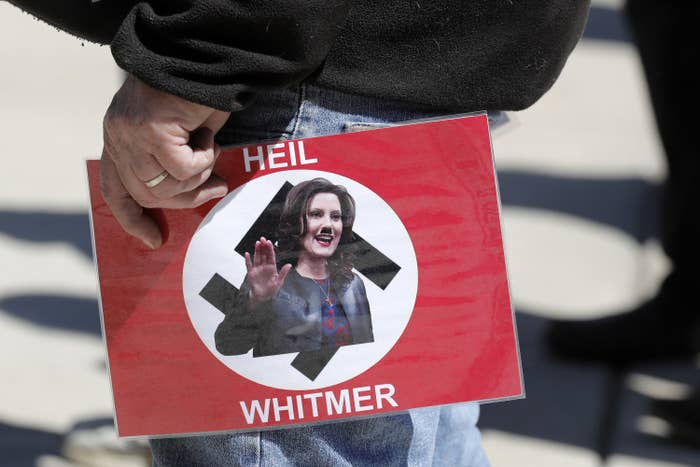 "Someone holds a sign with the flag of Nazi Germany; over the swastika in the center, Gretchen Whitmer appears with a photoshoppted Hitler mustache, appearing to make a ""Heil Hitler"" salute; the sign reads ""Heil Whitmer"""
