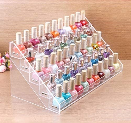 The plastic tiered organizer containing many bottles of colourful nail polishes