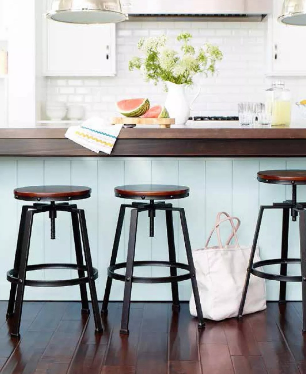 A round wooden top bar stool with black metal legs