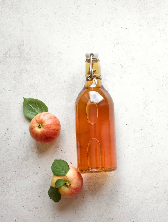 A bottle of apple cider vinegar on a countertop with two apples next to it.