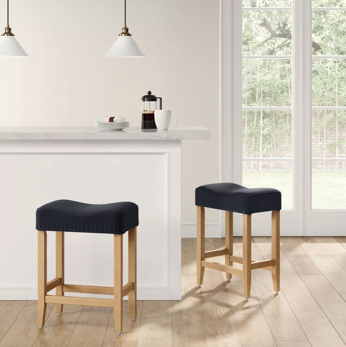 A pair of bar stools with navy cushions, nailhead detail, and wooden legs