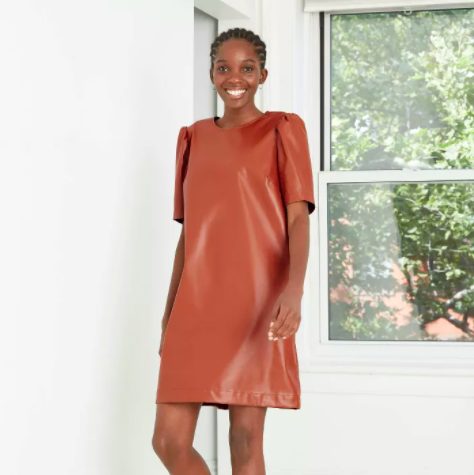 model wearing camel color faux leather shift dress with slightly puffy sleeves