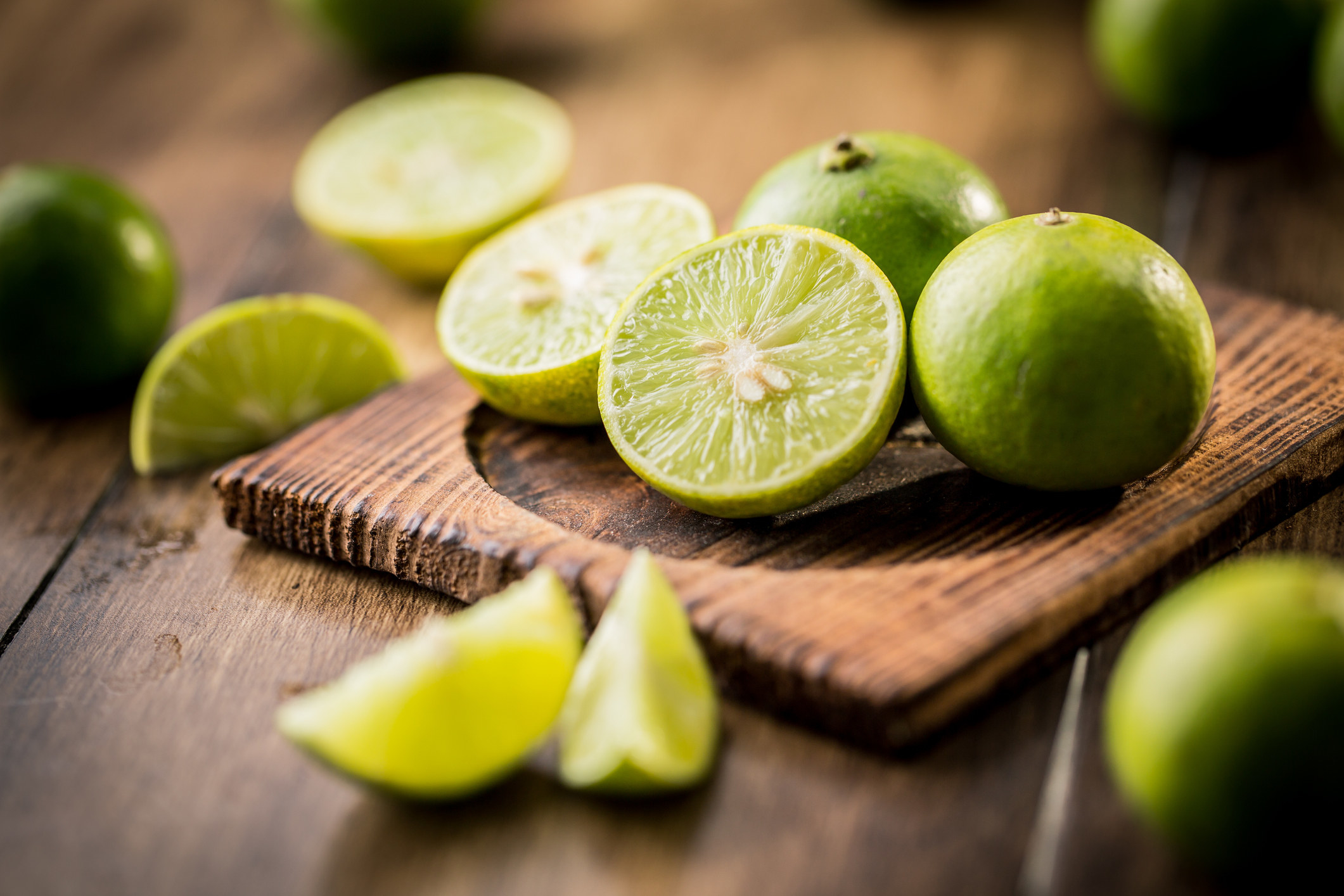 Sliced limes on a wooden cutting board.