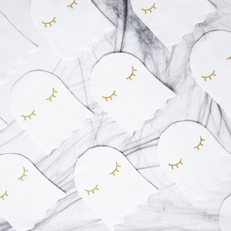 A set of napkins with ghosts that have gold eyelashes