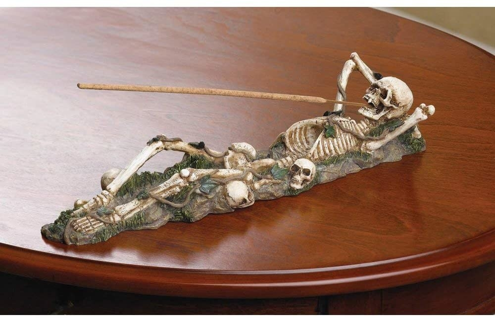 A skeleton lying down has a stick of incense coming out of its mouth