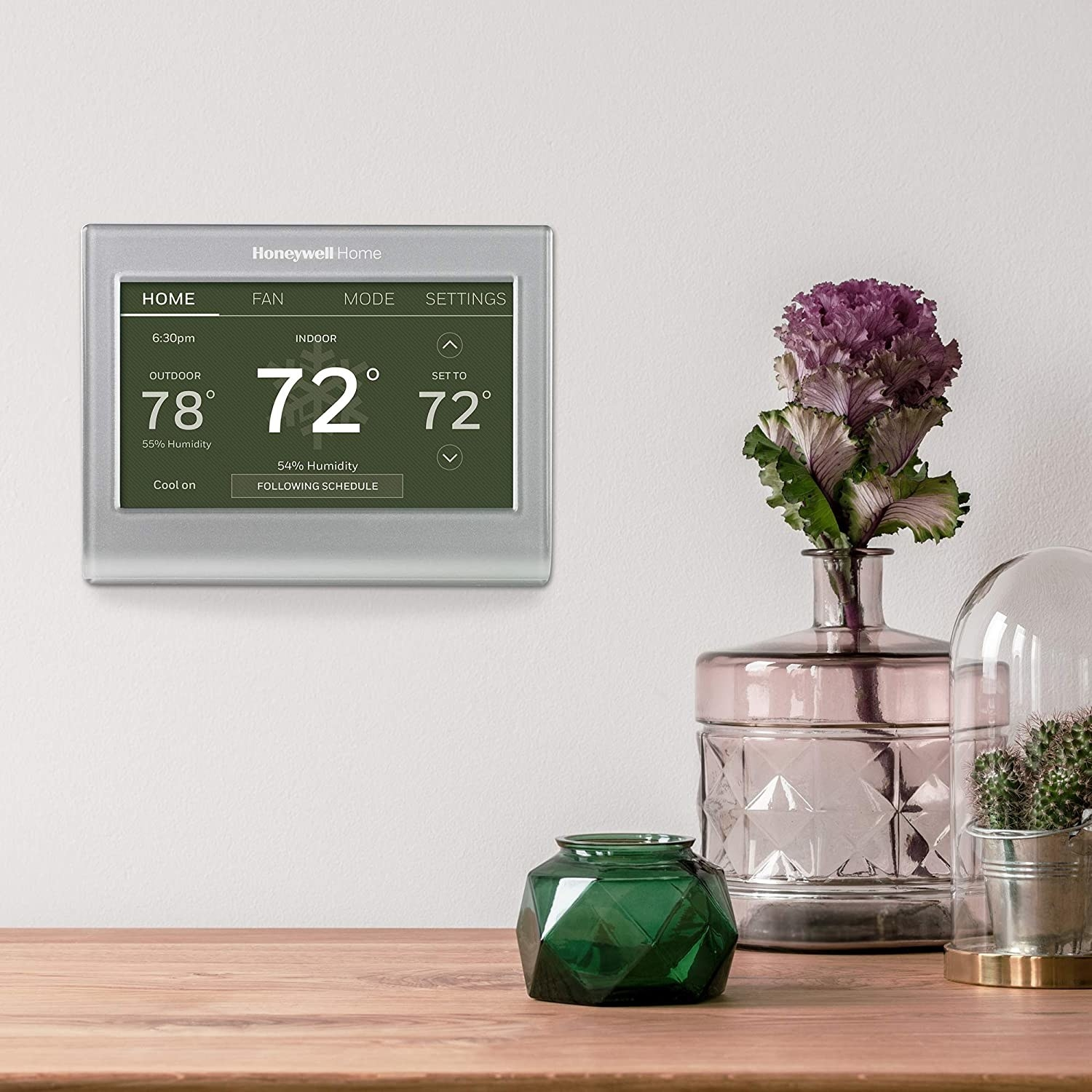 The thermostat hung on a wall next to some geometric glass vases