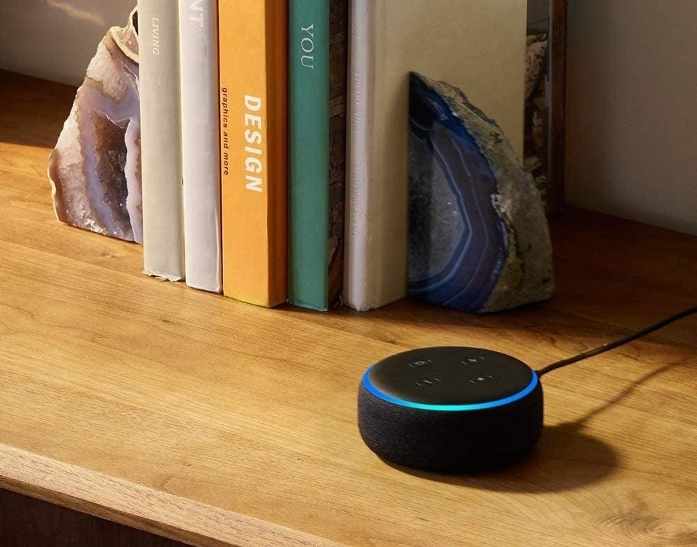 A smart speaker beside a bookshelf