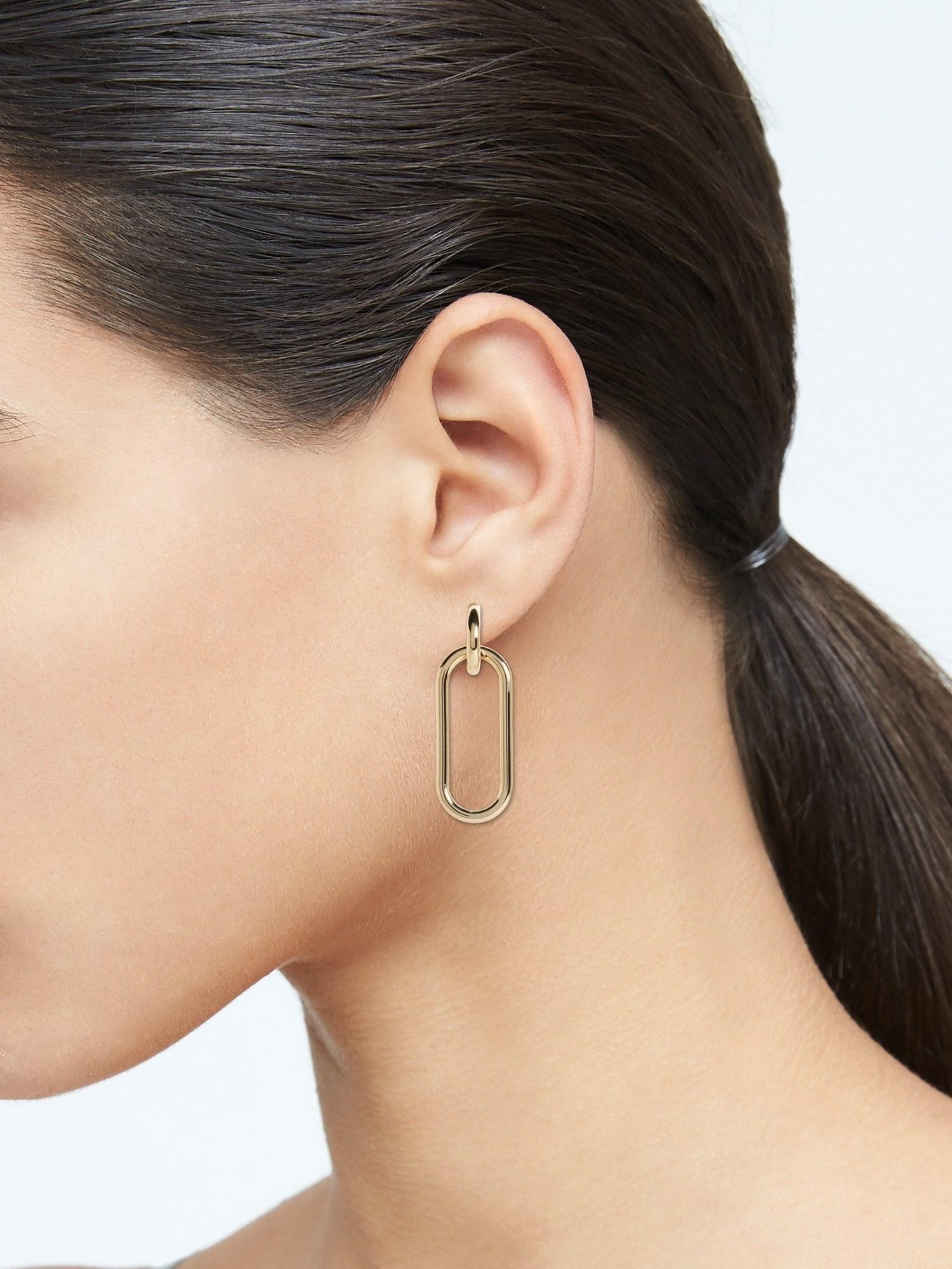 Model wearing the oval-shaped link earrings in gold