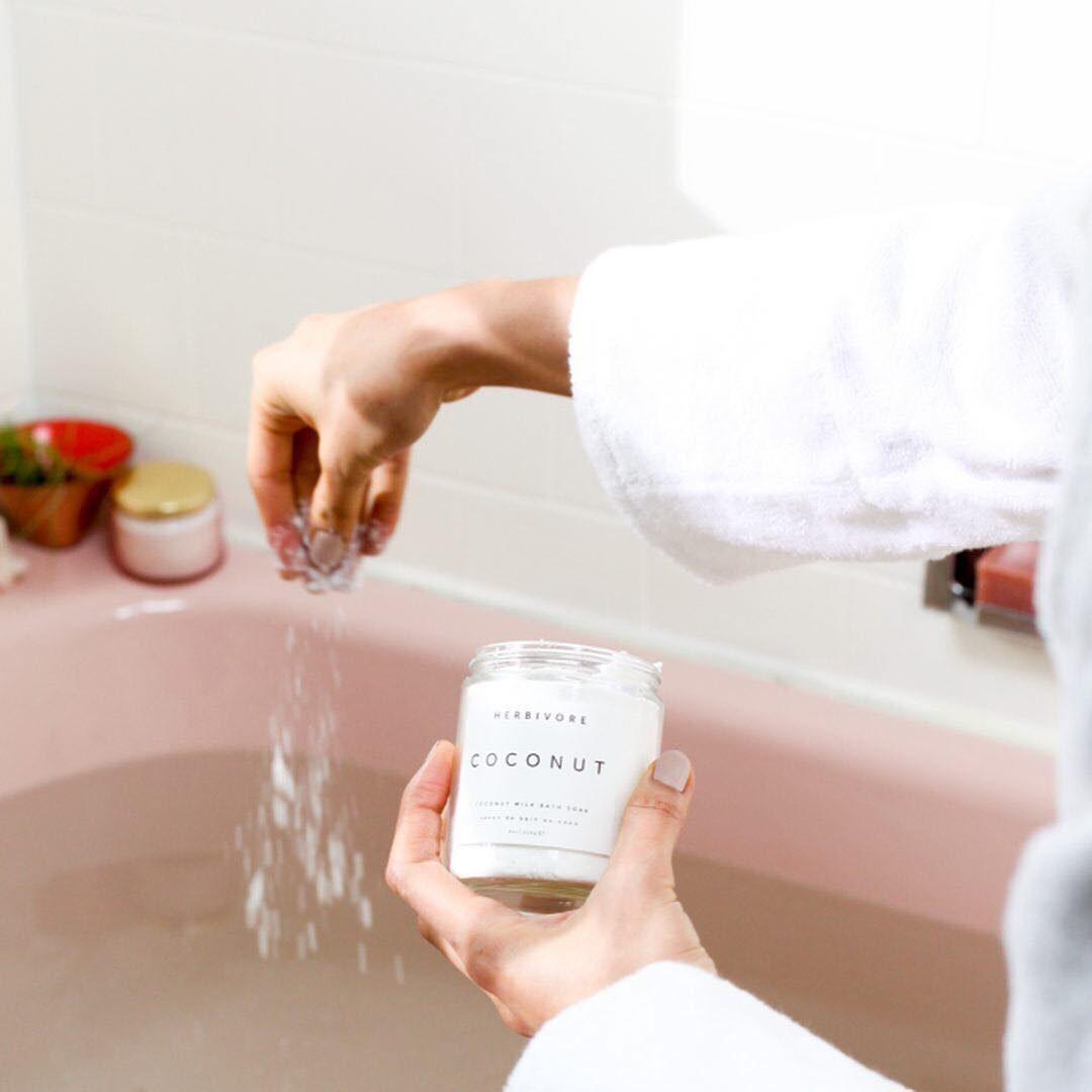 A person sprinkles bath salt into a bath