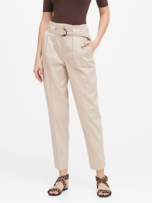 Model wearing the ankle-length pants with a pleated waist, removable slider belt, and side pockets