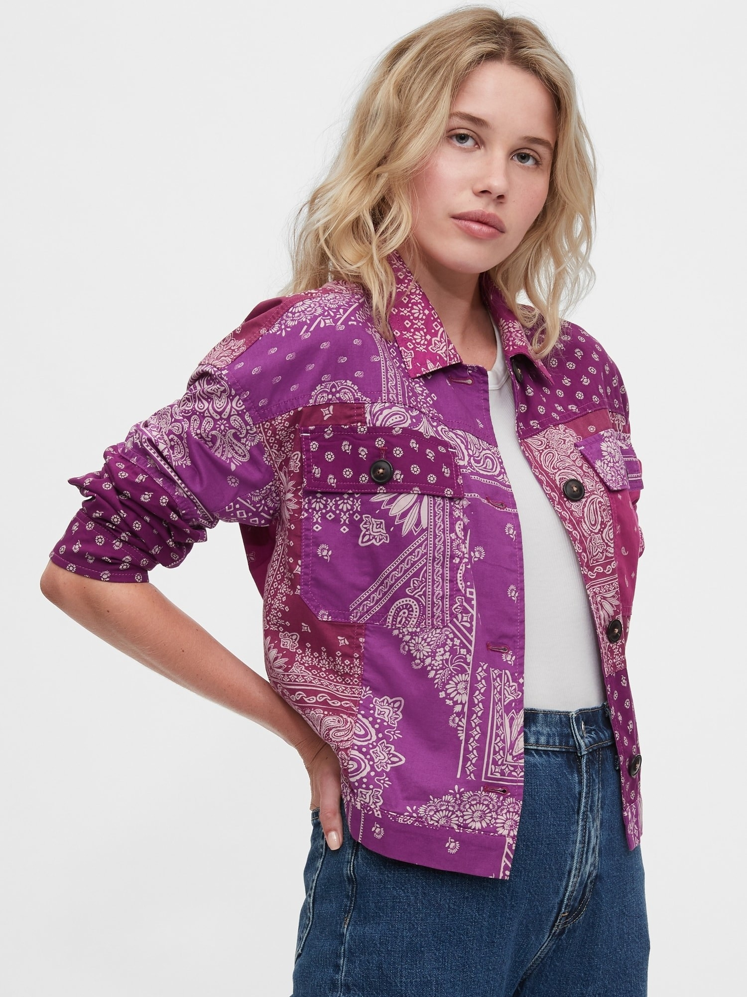 A model wearing the collared, button front, purple and pink jacket in mixed paisley and bandana-esque prints with jeans