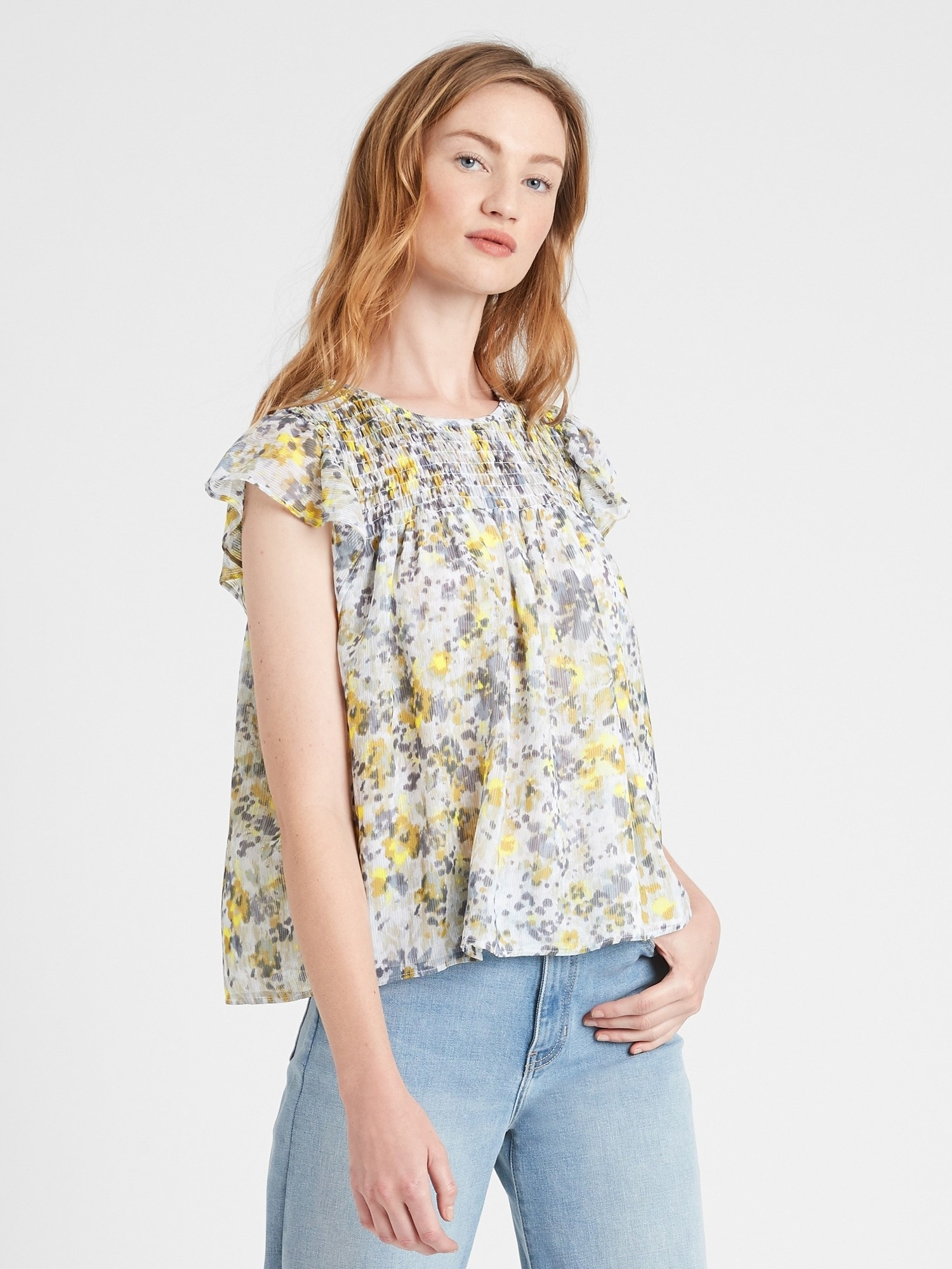 A model wearing the short flutter sleeve yellow and gray floral top with jeans