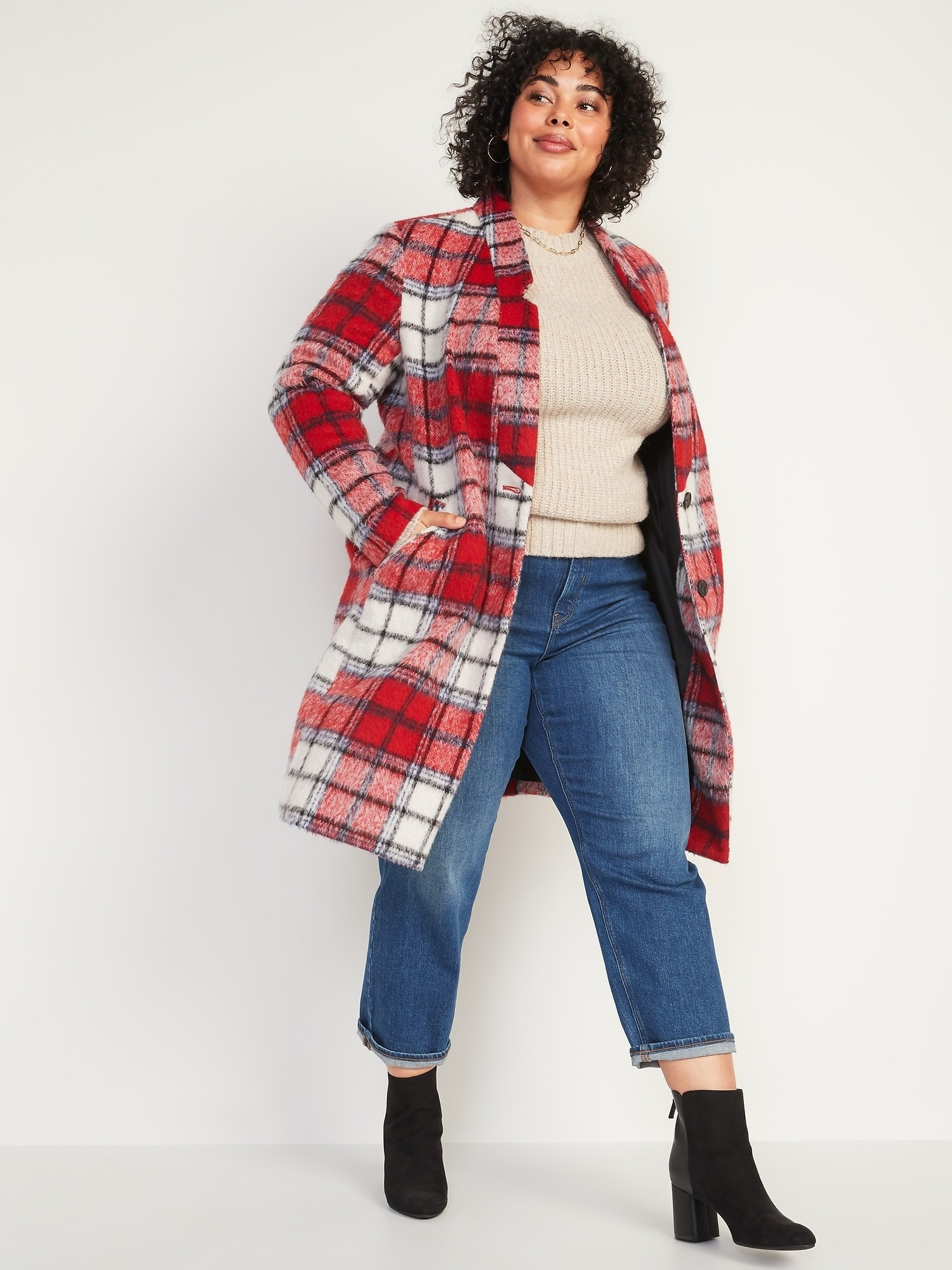 A model wearing the red and white plaid coat that hits just above the knee with jeans and booties
