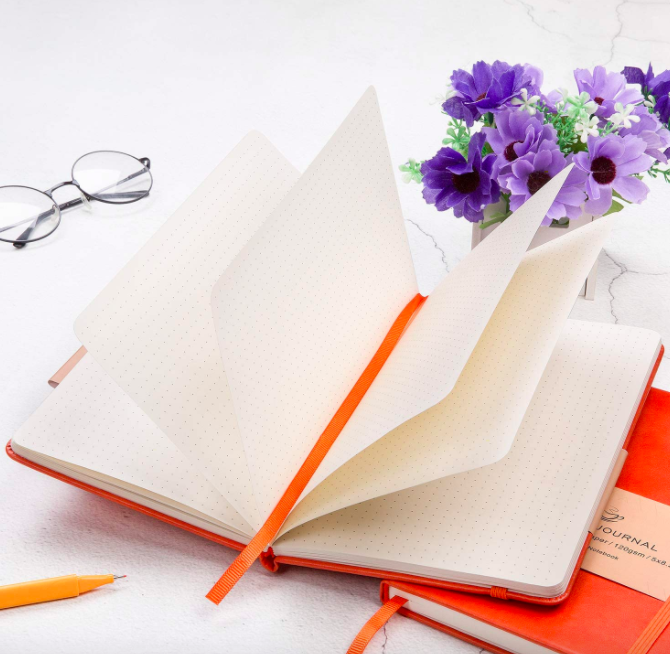 Small orange journal with blank pages on a table next to an orange pen, glasses, and violet flowers