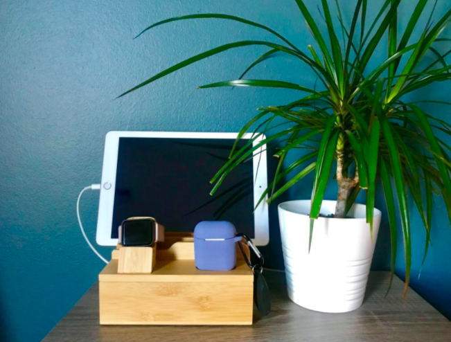 Bamboo charging dock juicing up a pink and black smartwatch, AirPods, and a white tablet next to a white vase and plant on a table