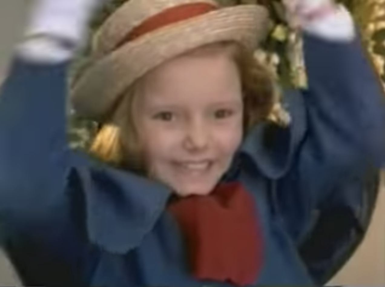 Hatty Jones smiles and presses her hat to her head as Madeline