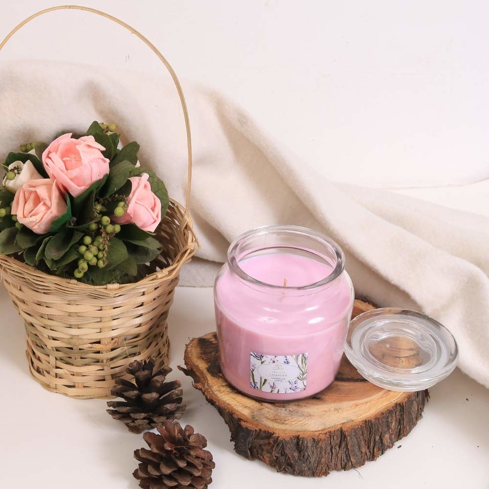 The candle placed near some pinecones and a basket of flowers.