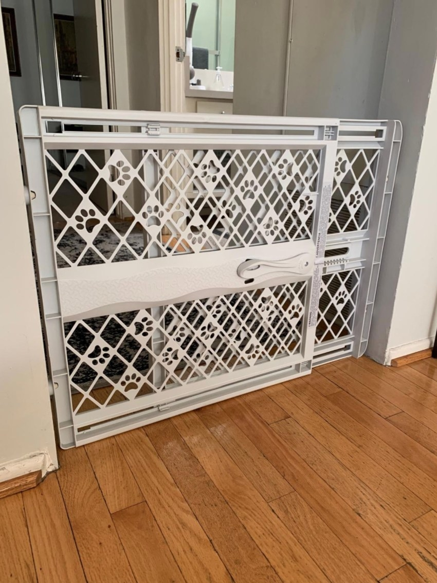 A reviewer's white puppy gate being with the extendable feature being used