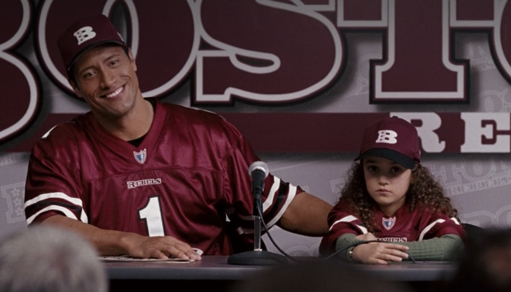 """The Rock and Madison Pettis wear football jerseys and ball caps as Joe and Peyton in """"The Game Plan"""""""