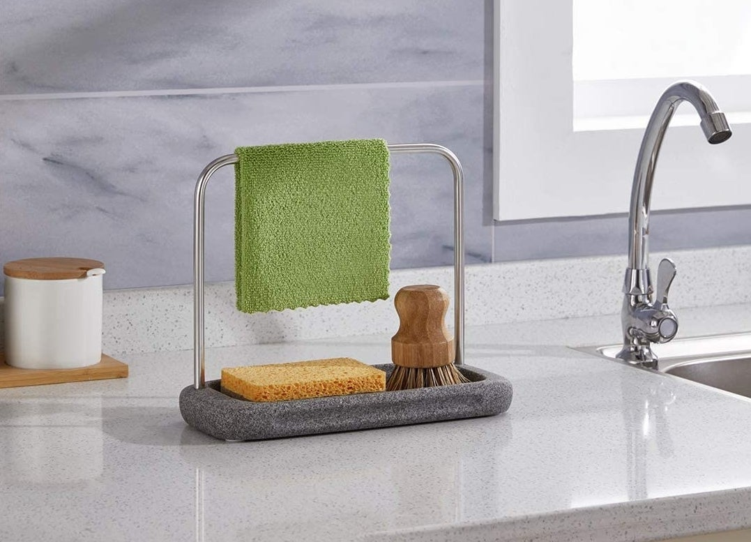 The caddy holding a brush and a sponge with a dish rag draped over its tiny rail