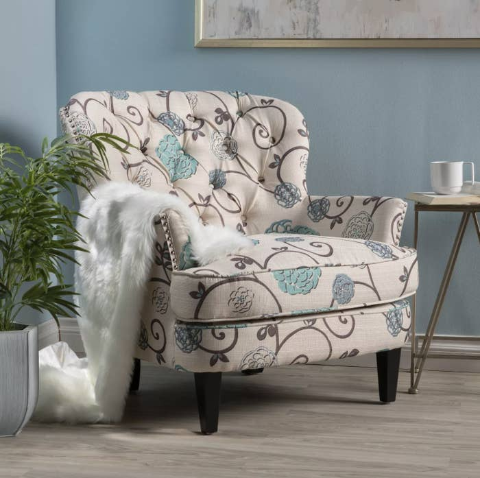 A floral accent chair with a blanket on top in a living room