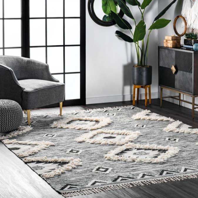 Shaggy Moroccan-style gray, white, and black square rug next to gray armchair, black planter, and black and gray chest