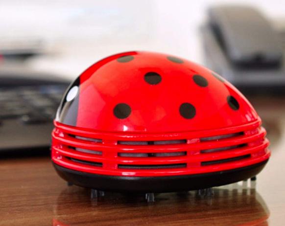 Red ladybug desk vacuum sucks up crumbs from a desktop