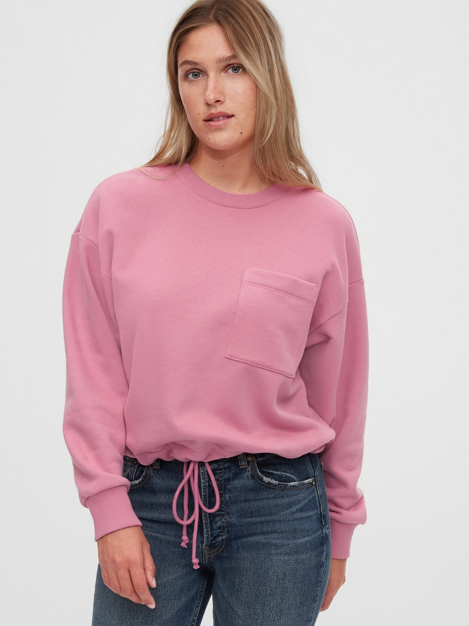 The pink sweatshirt, which has a chest pocket and drawstring on the bottom