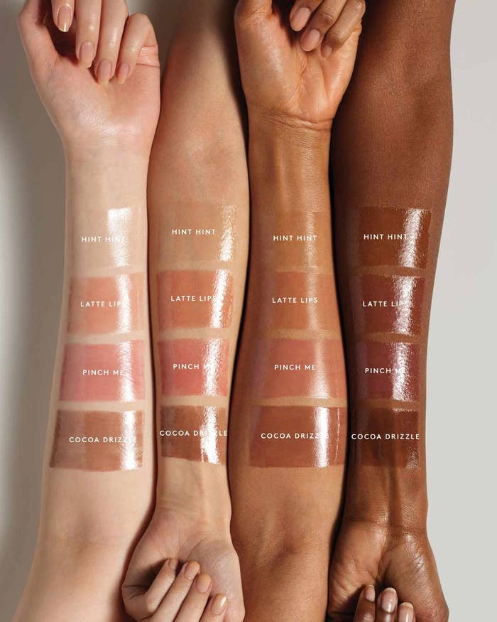 The four shades (brown, pink, peach, and clear-pink) swatched on four arms with different skin tones