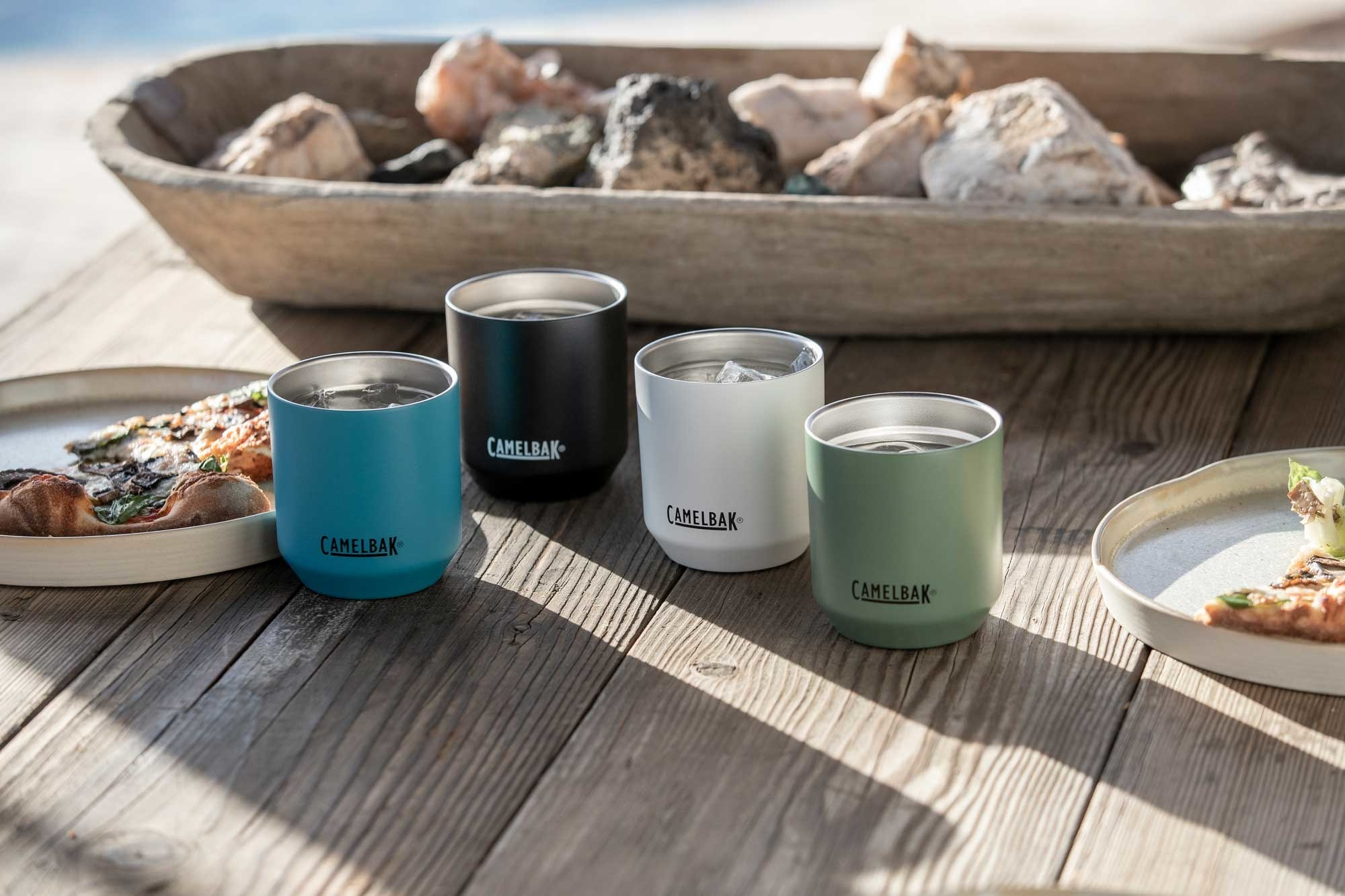 Four of the stainless steel tumblers in different colors: blue, black, white, and green