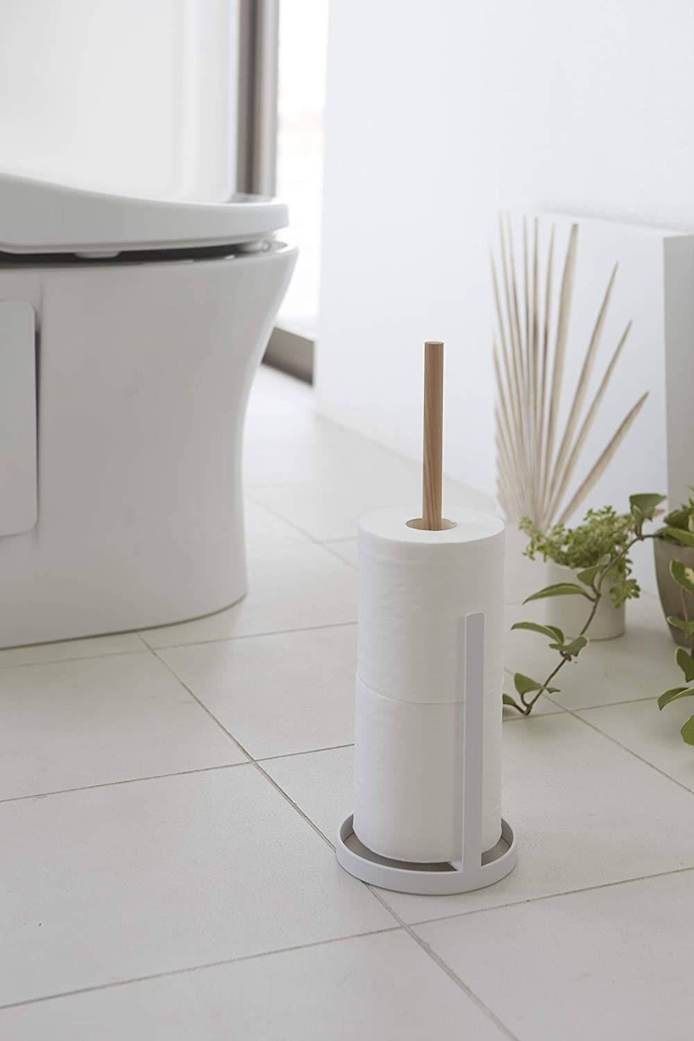 bathroom with white and wood toilet paper towel in a white bathroom