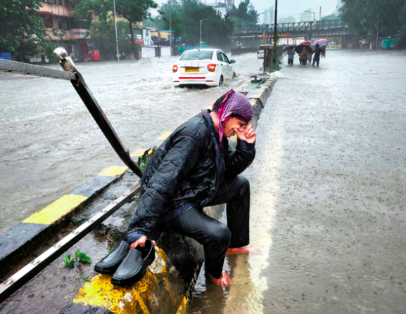 A man cries on the street while it rains