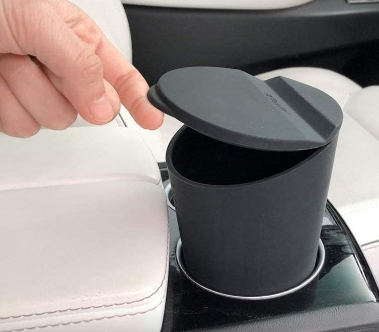 A person opening the cup holder trash can
