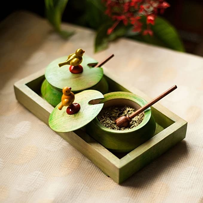 Green chutney jars in a wooden tray.