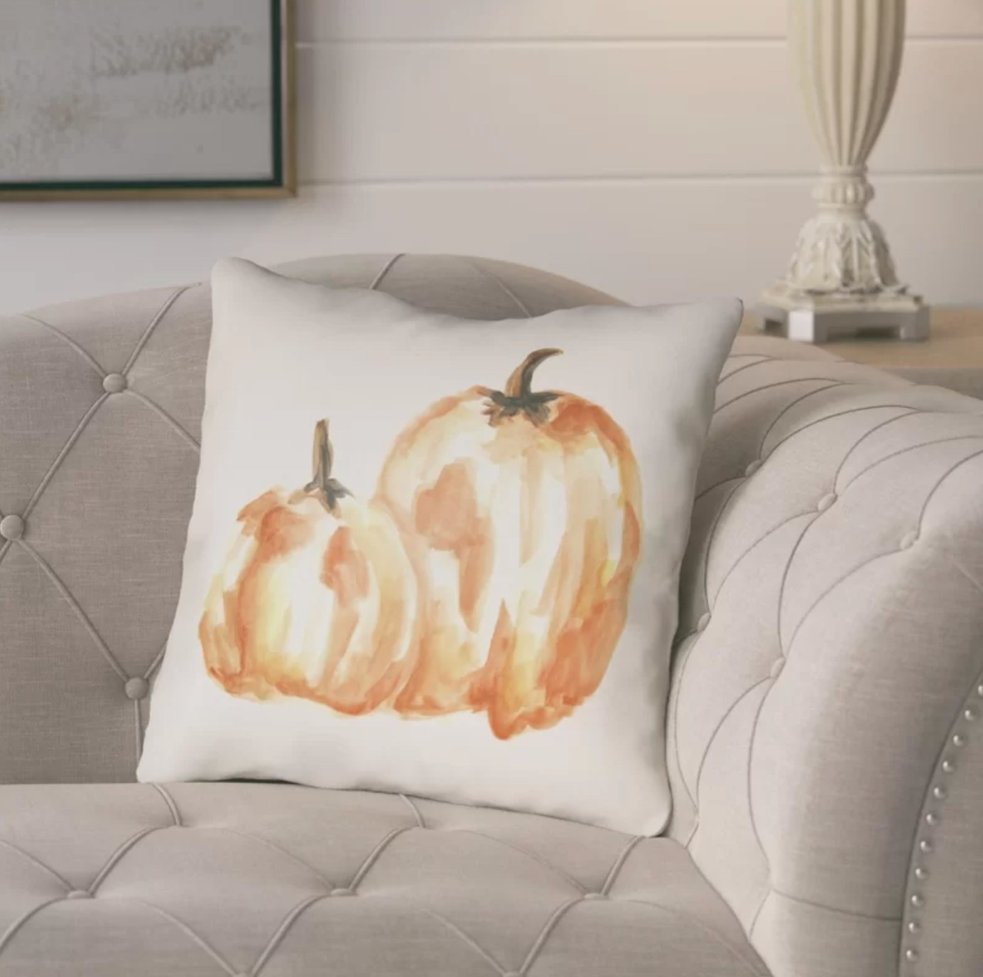 The white throw pillow with an orange pumpkin design