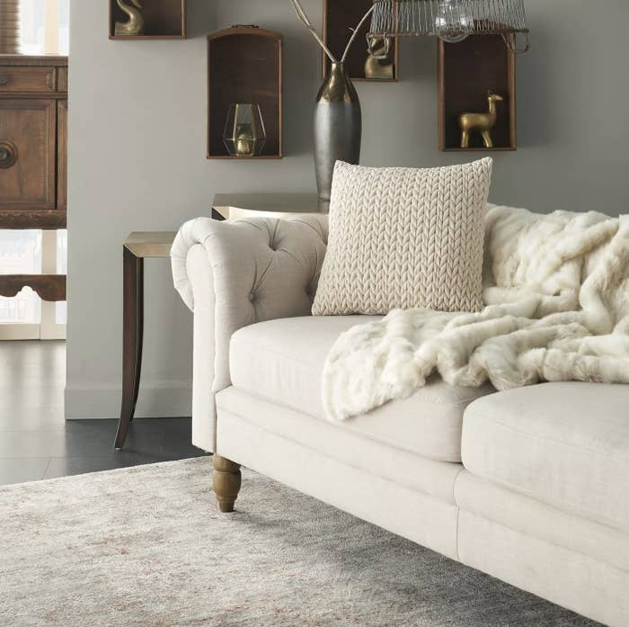 A cream quilted chevron throw pillow on a couch in a living room
