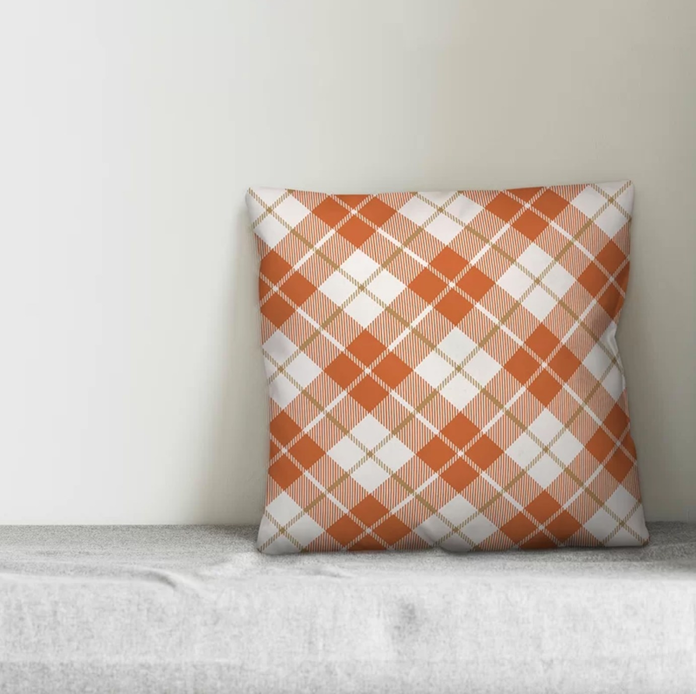 The plaid throw pillow in orange and white