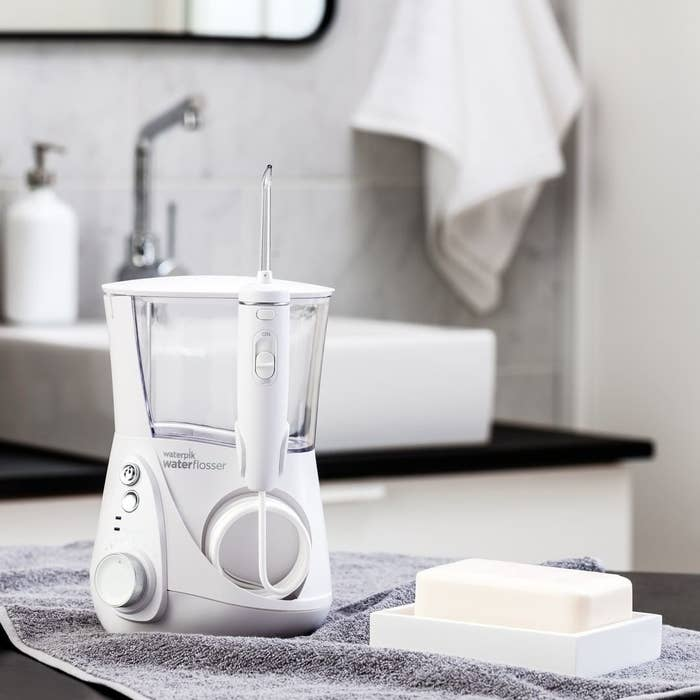 A close up of the water flosser next to a bar of soap in a bathroom
