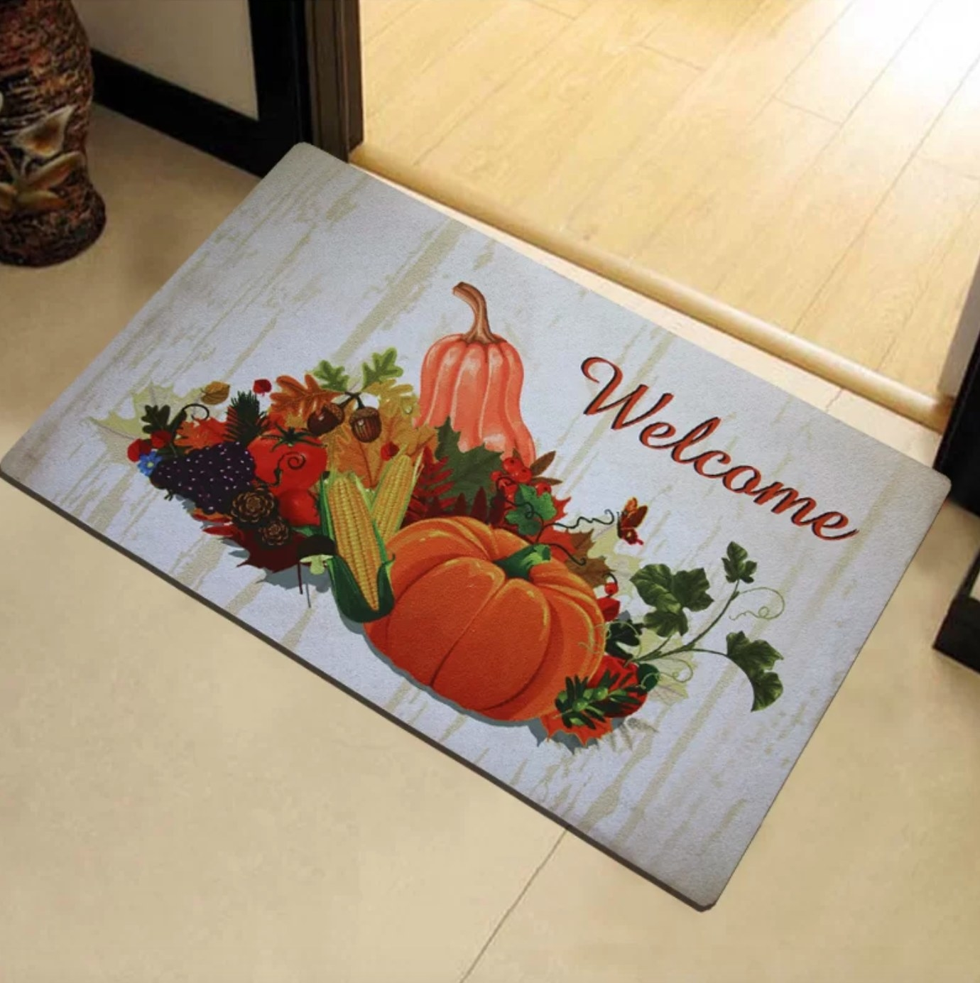 The nonslip outdoor doormat featuring fall vegetables and colorful leaves
