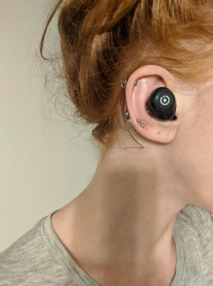Reviewer wears black wireless earbud in their right ear