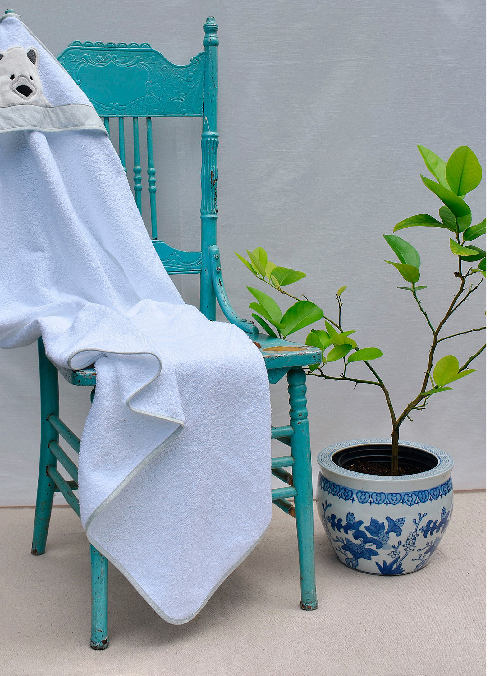A hooded baby towel resting on a small chair