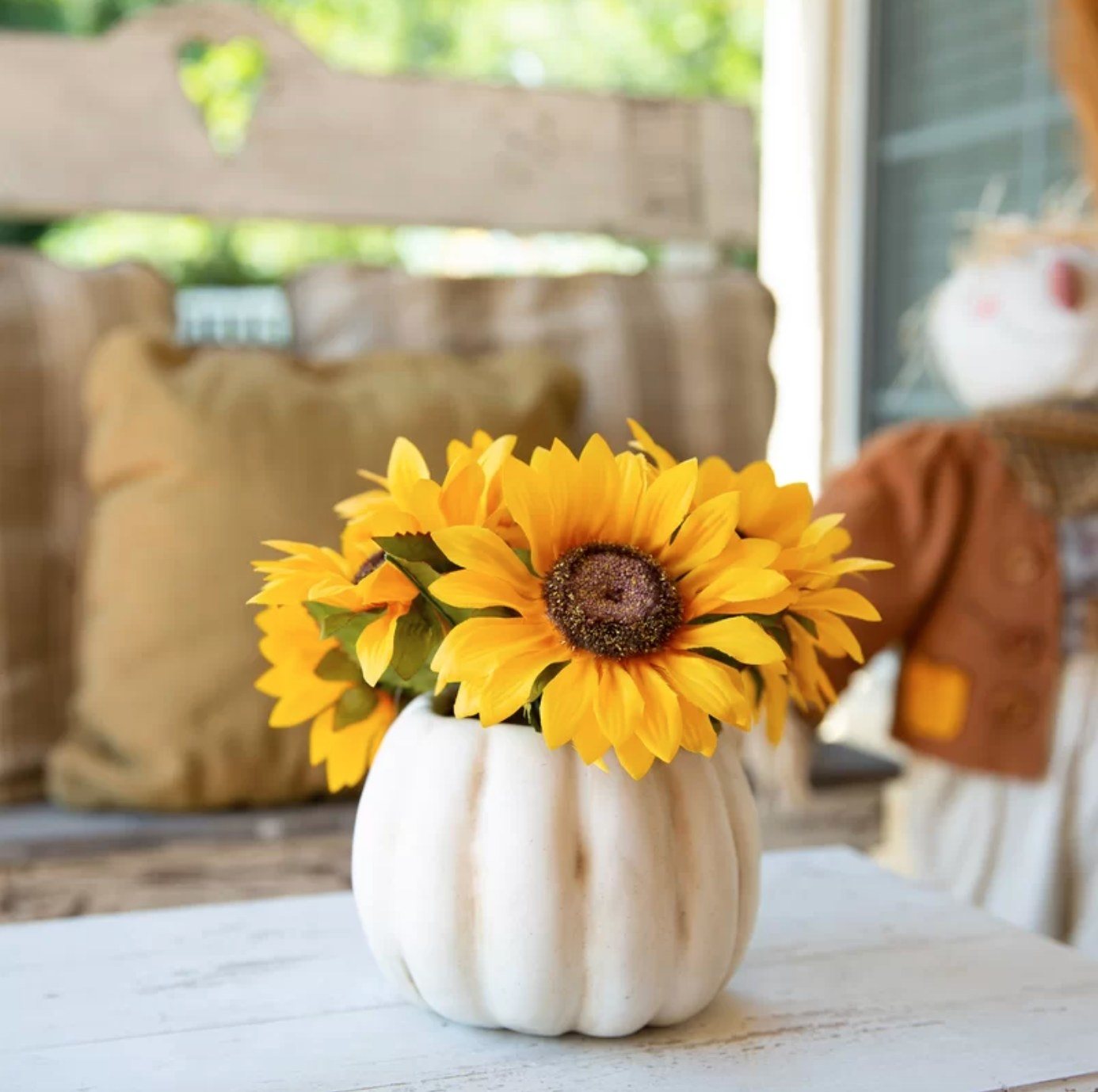 The sunflower floral arrangement in a white pumpkin pot