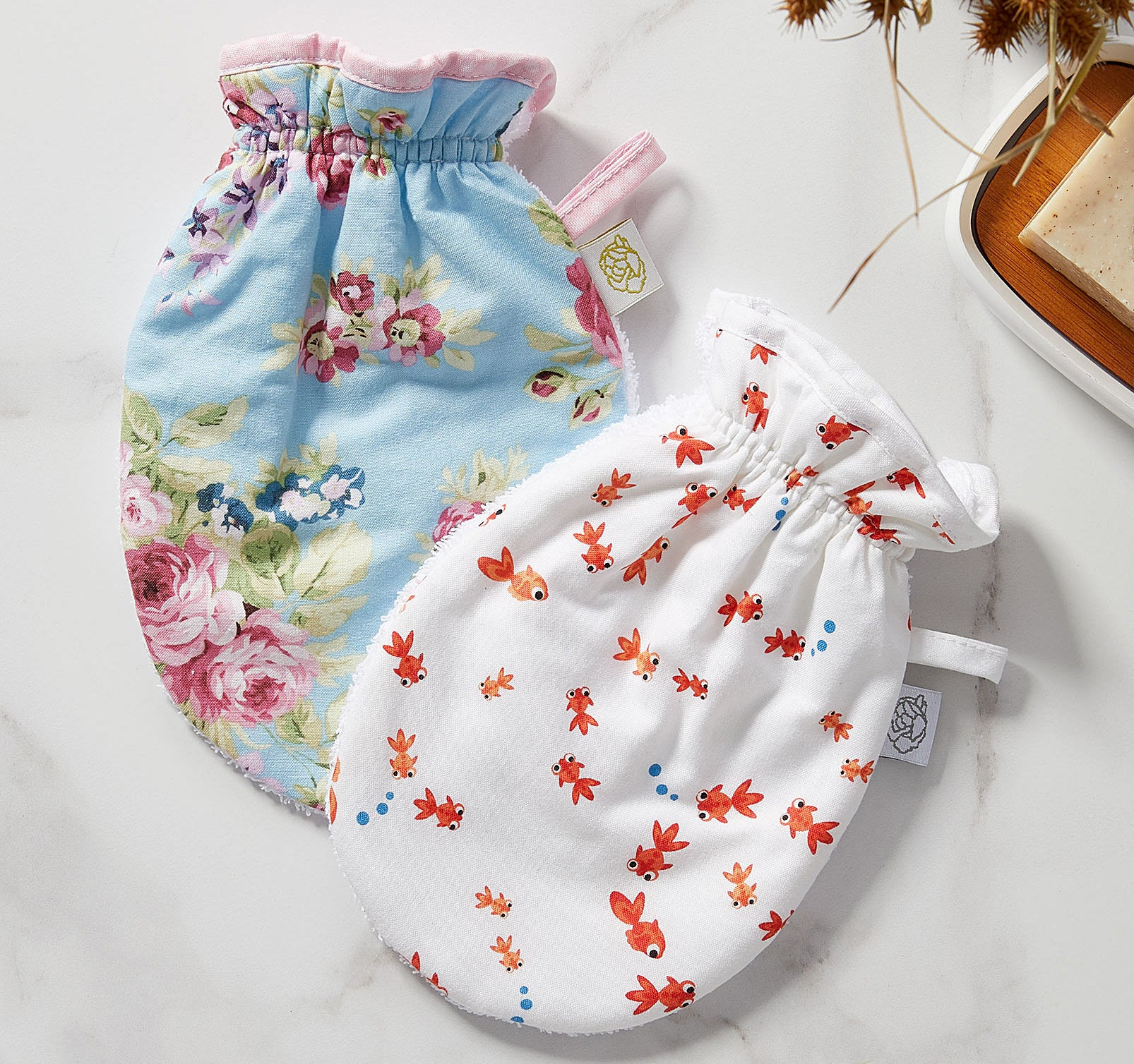 Two soft cloth bath mittens on a plain background