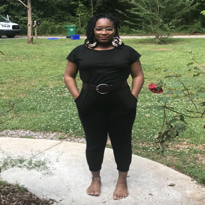 reviewer wearing the black jumpsuit with belt