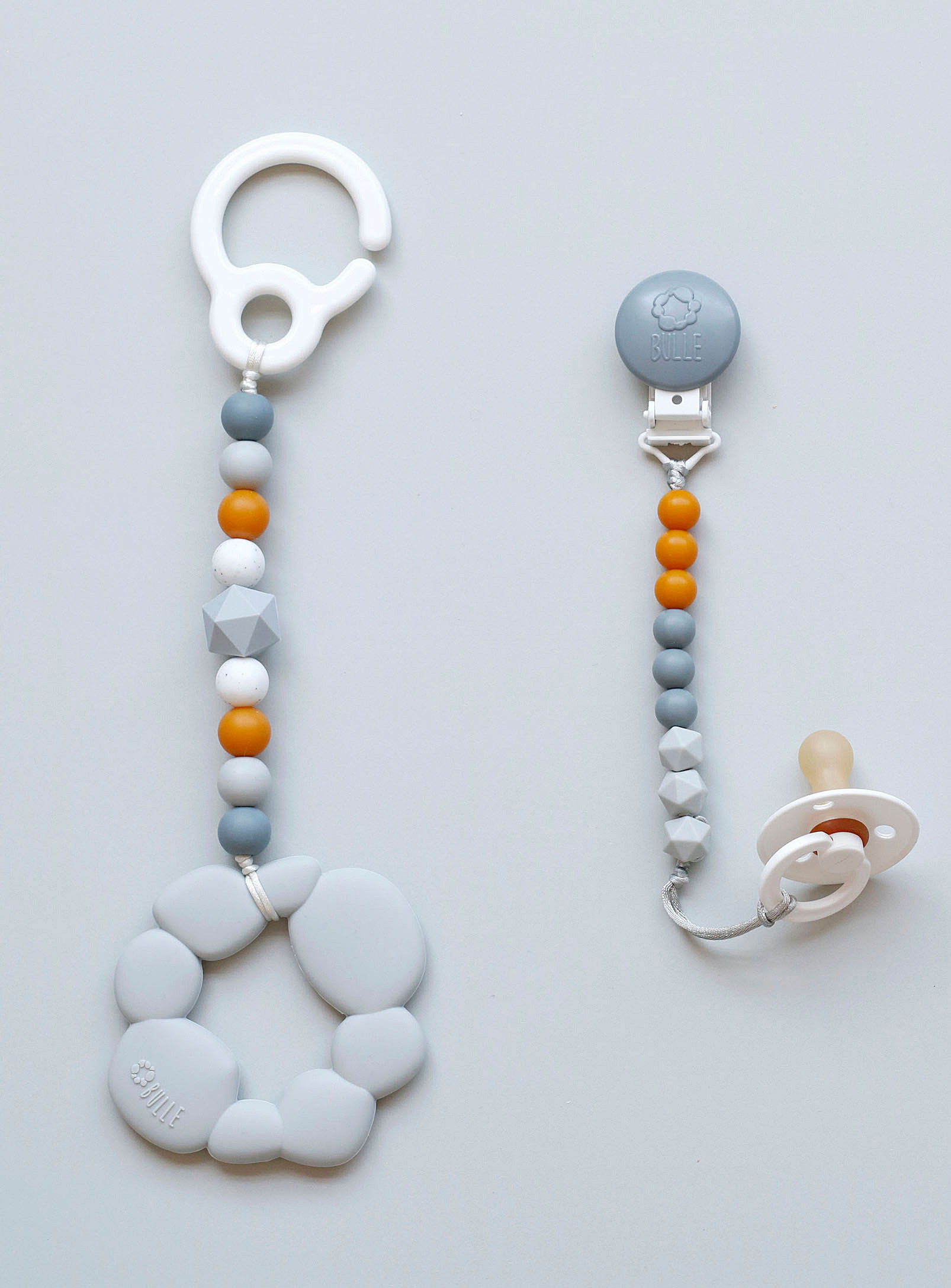 Two pacifier clips with a beaded silicone rope