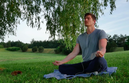 A person sits in a field and meditates
